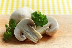 White mushrooms. Cut champignons mushrooms and green fresh parsley on chopping board Stock Photo