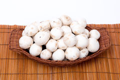 White mushrooms in a basket isolated on white Stock Photo