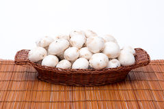 White mushrooms in a basket isolated on white Royalty Free Stock Photography