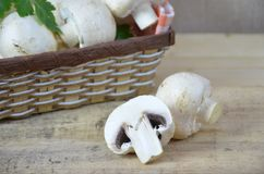Fresh white mushrooms champignon in brown basket on wooden background. Top view. Copy space royalty free stock images