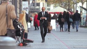 White musician plays the accordion on street with black man in suite stock video footage