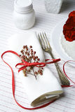 White napkin decorated with red ribbon Christmas plant, table se Stock Photo