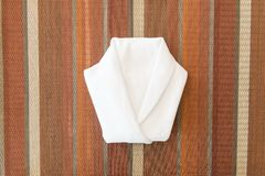 White napkin folded into a shirt on dinner table Royalty Free Stock Image