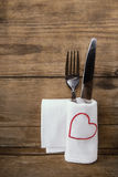 White napkin with a red heart and a set of cutlery on an old woo Royalty Free Stock Photo