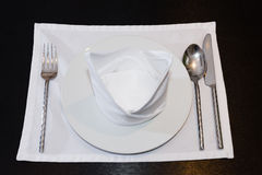 White napkins folded as triangles on plates with silverware Royalty Free Stock Images