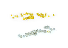 White natural diamonds and yellow synthetic diamonds. The scattered white natural diamonds and yellow synthetic diamonds on a white background Royalty Free Stock Images