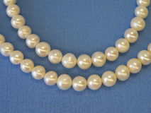 White natural pearls. Natural white pearls necklace isolated on blue fabric Royalty Free Stock Images