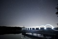 White Neon Lights Lit on Wooden Dock Above Body of Water Under Starry Night Sky Royalty Free Stock Image