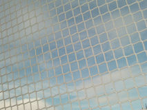 White net close up. Low angle view of white net with sky and clouds in background Royalty Free Stock Image
