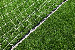 White net for football lying on grass Royalty Free Stock Image