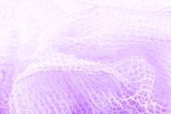 White netting on lavender. Closeup of a tangled soft white netted fabric with the color lavender showing through Stock Images