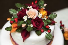 White new beautiful colorful wedding cake with flowers. White new beautiful tasty wedding cake with geometric triangular orange and burgundy patterns decorated Stock Photo