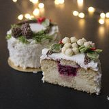 White New Year or Christmas cake decorated with cream poinsettia flowers, pine cones, cotton and spruce twigs on a black royalty free stock image