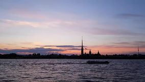 White nights in St. Petersburg. Historic centre. The ship floats on the Neva river. Silhouette of the Peter and Paul fortress. Against the purple sunset. A stock video