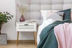 White nightstand in pastel bedroom. Close-up of dark vase with flowers on white nightstand next to bed with pink and green bedsheets in pastel bedroom interior Stock Photography