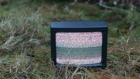 TV no signal in grass. White noise on analogue TV set in the grass stock video footage