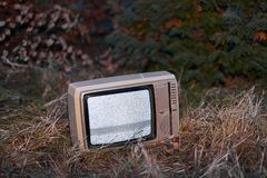 TV no signal in grass. White noise on analogue TV set in outdoor environment royalty free stock photography