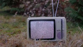 TV no signal in grass. White noise on analogue TV set in outdoor environment stock video footage
