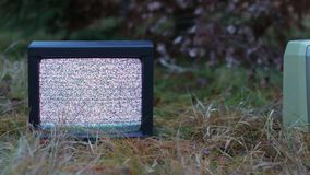 TV no signal in grass. White noise on analogue TV sets in outdoor environment, panning shot stock video