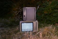 TV no signal in grass. White noise and nothing on two analogue TV sets in outdoor environment royalty free stock photo