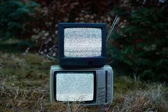TV no signal in grass. White noise and nothing on two analogue TV sets in outdoor environment stock image