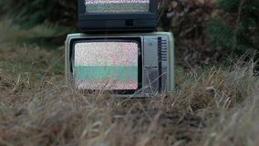 TV no signal in grass. White noise on two analogue TV sets on top of each other in outdoor environment stock footage