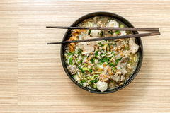 White noodle and soup pork in black bowl with wood stick Royalty Free Stock Photo