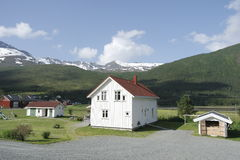 White Norwegian house amid the green hills Royalty Free Stock Image