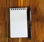 Note book Black pen on wooded table. White Note book Black pen on wooded table royalty free stock photo