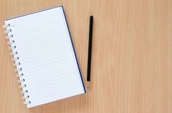White note book and black pencil on beech color background with Royalty Free Stock Photography
