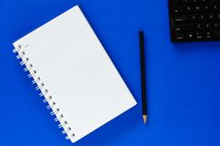 White note book and black pencil and black keyboard on blue colo Stock Image
