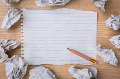 White note book paper with  pencil and crumpled paper. On a wooden desk Royalty Free Stock Photo