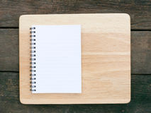 The white note book and wooden board on old deep brown planks Stock Image