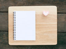 The white note book and wooden board on old deep brown planks Royalty Free Stock Photography