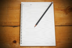 White note book for your text or image and a pencil on wooden desk. White note book for your text or image and a regular pencil on a wooden desk Stock Photo