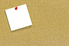 White note on a cork noticeboard. A blank memo or sticky note tacked to a cork notice board with copyspace Stock Photos