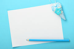 White note with toy heart and pencil on blue background Royalty Free Stock Photos