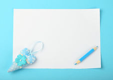 White note with toy heart and pencil on blue background Stock Image