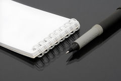 White notebook. Pen, black background stock images