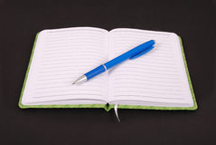 White notebook and blue pen. White notebook with blue pen isolated on black background Royalty Free Stock Photos