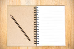 White notebook with frangipani flower on the wood Stock Photography