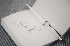 White notebook with motivating quote on material background. Life is good.  Stock Photo