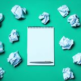 White notebook with pen on a green background among paper balls. The concept of generating ideas, inventing new ideas. Paper balls. Are all around. Searching of stock images