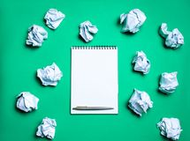 White notebook with pen on a green background among paper balls. The concept of generating ideas, inventing new ideas. Paper balls royalty free stock photos