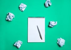 White notebook with pen on a green background among paper balls. The concept of generating ideas, inventing new ideas. Paper balls. Are all around. Searching of stock photo