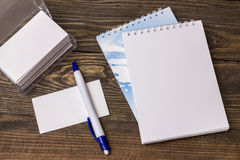 White notebook with pen. White notepad with pen lying on a wooden table Royalty Free Stock Photos