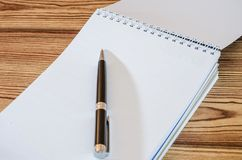 White notebook and pen on a wooden background, Close-up. stock photo