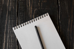 White notebook and pencil on a wooden background Royalty Free Stock Image