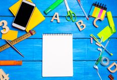 A white notebook on the student`s desk among the school supplies. Space for text, copy space. The concept of education royalty free stock images