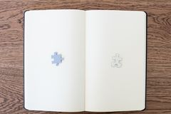 A white notebook on a wooden table with two puzzle pieces, one w royalty free stock photography